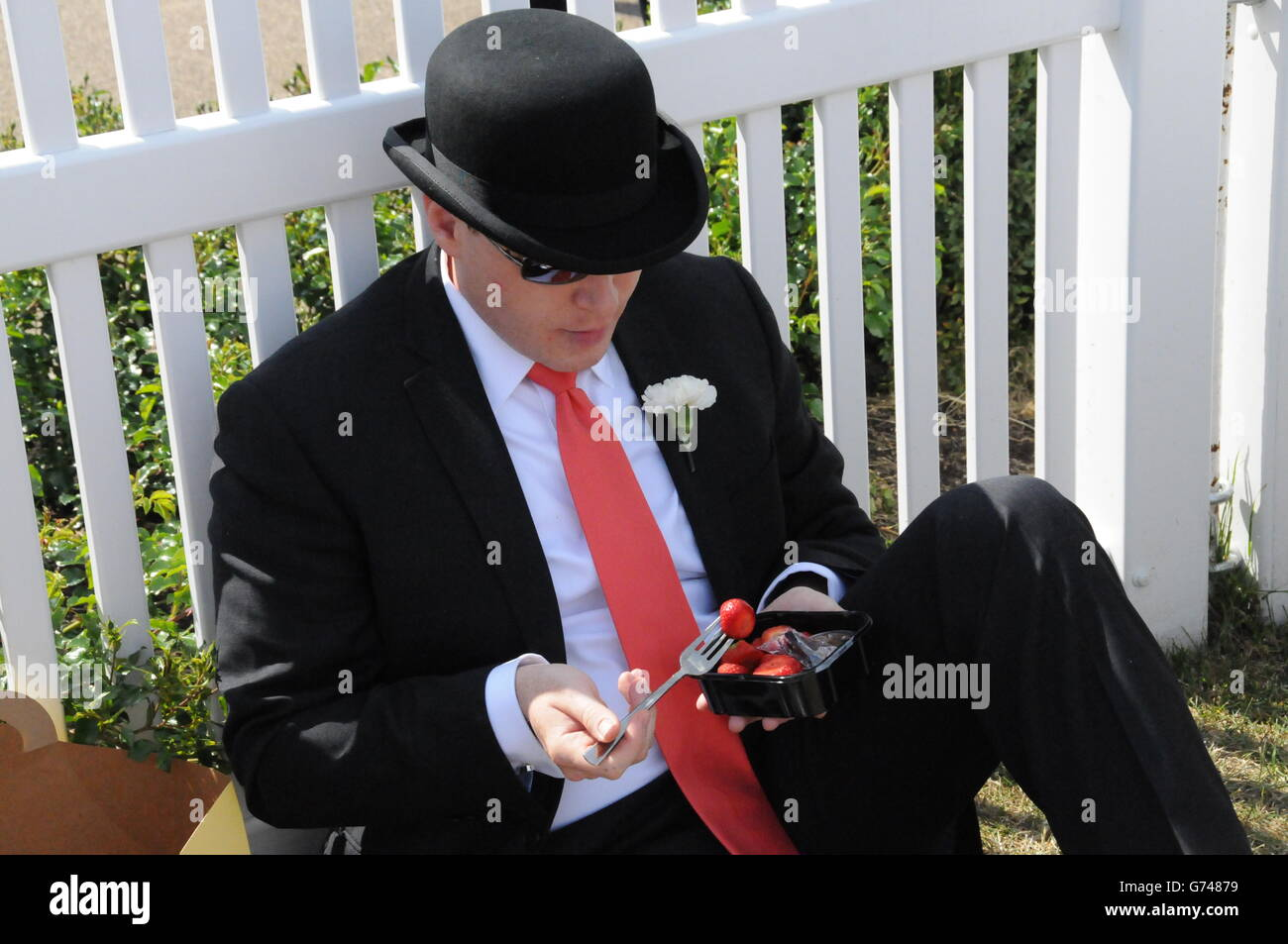 An Englishman tucks into strawberries, on a balmy June afternoon, at the Royal Ascot race meeting. - Stock Image