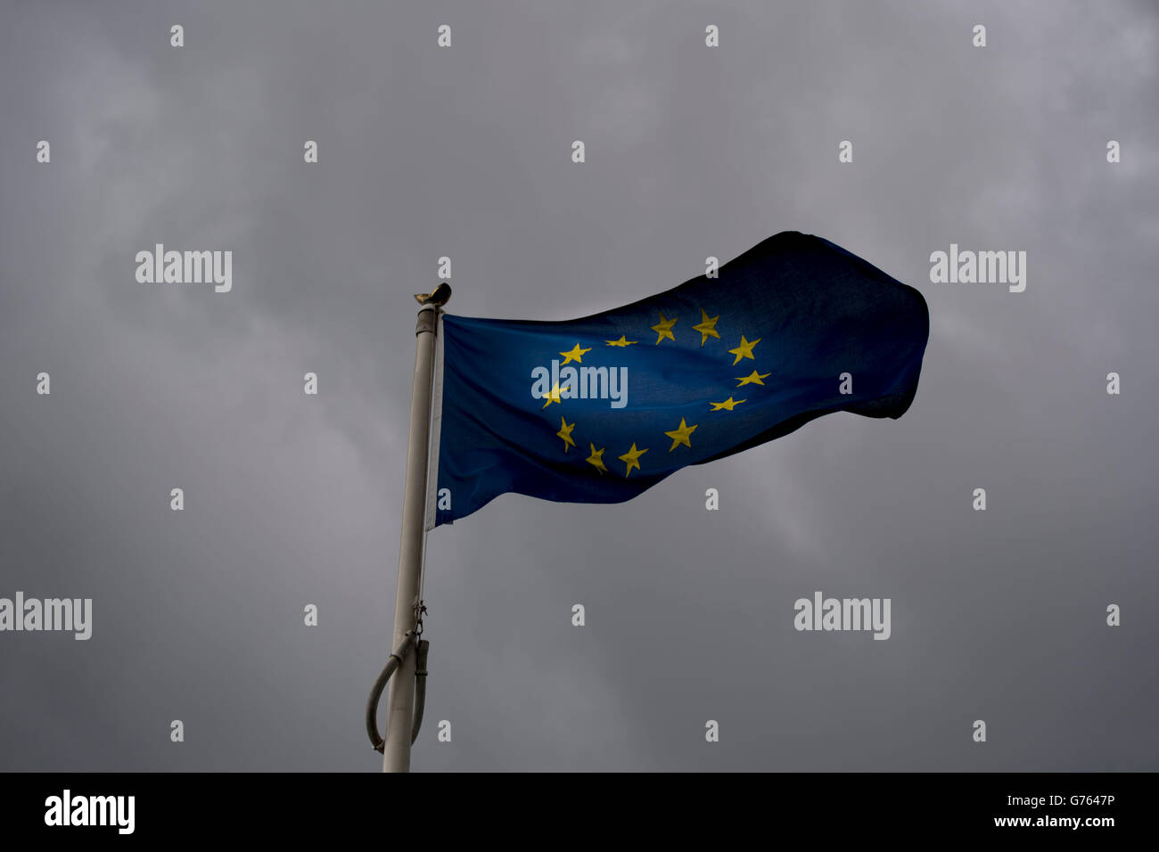 European Union (EU) flag blowing in the wind with dark storm clouds behind. Britain left the EU in a recent referendum. - Stock Image