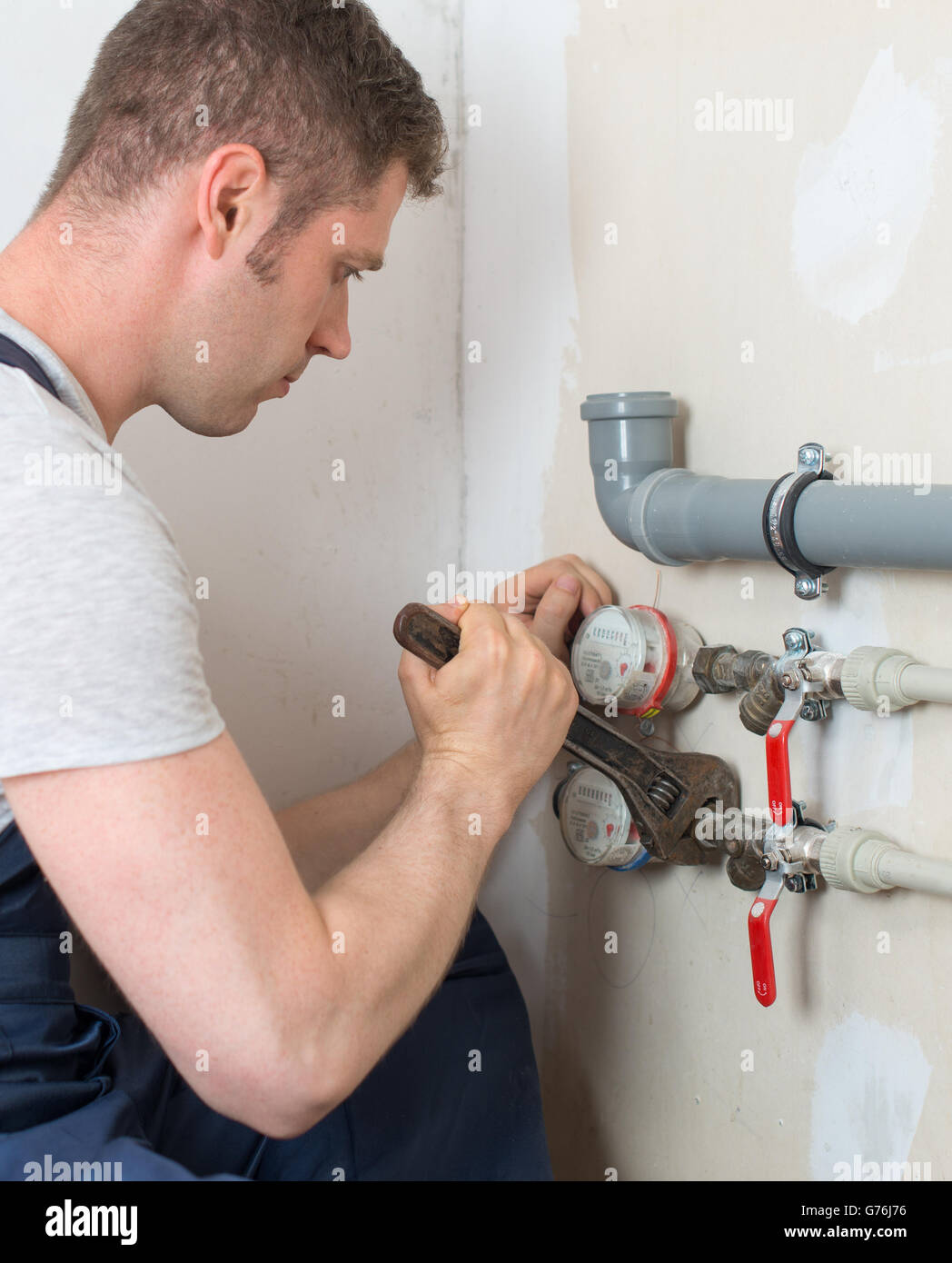 Male plumber assembling water pipes. - Stock Image