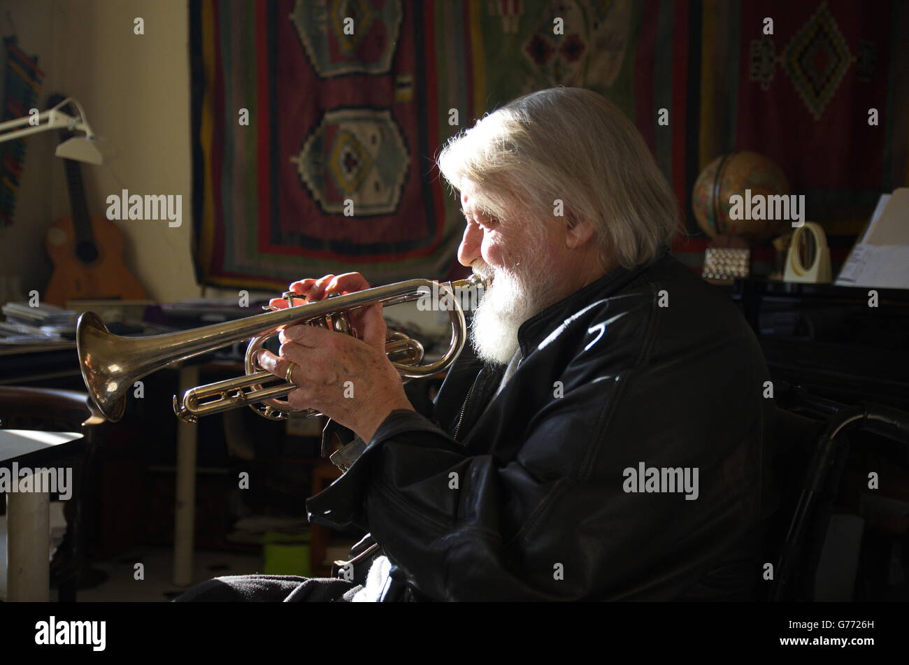 Strong sidelighting captures musician Robert Wyatt blowing his trumpet at his studio in Lincolnshire. - Stock Image