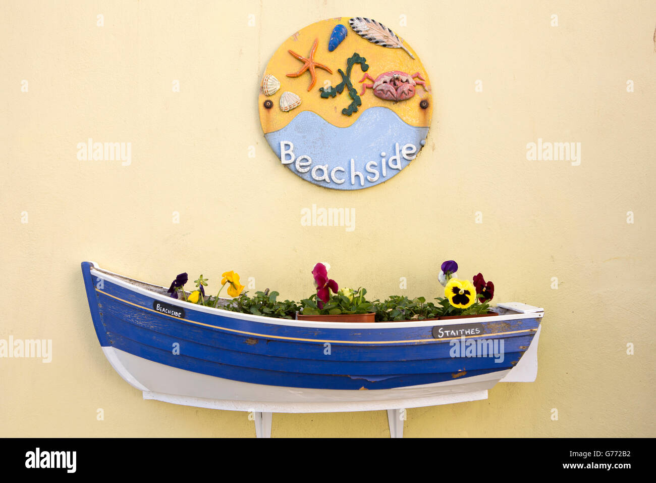 UK, England, Yorkshire, Staithes, boat shaped flower planter and ceramic Beachside house name plate Stock Photo