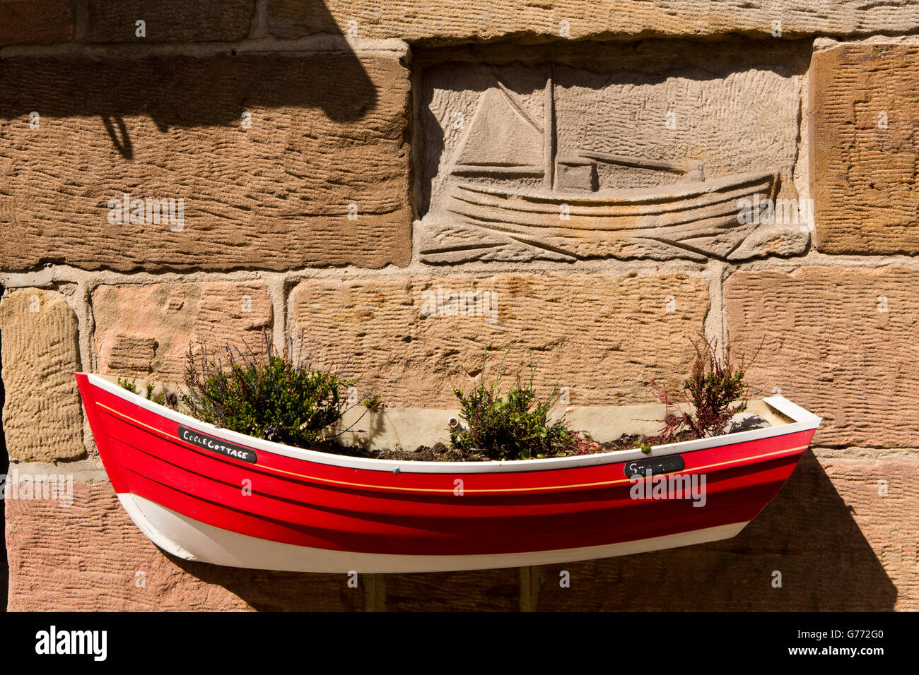 UK, England, Yorkshire, Staithes, High Street, Coble Cottage, red boat shaped flower planter - Stock Image