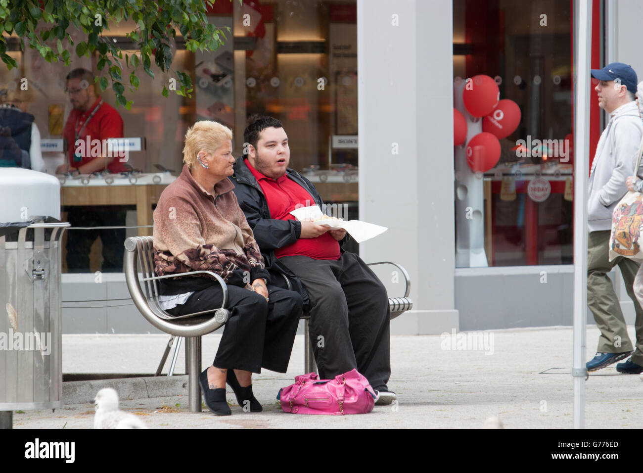 Clacton Town Centre couple eating chips while seated in Clacton, Essex - Stock Image