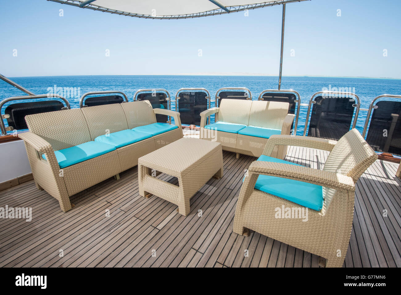 rear teak deck of a large luxury motor yacht with chairs sofa table