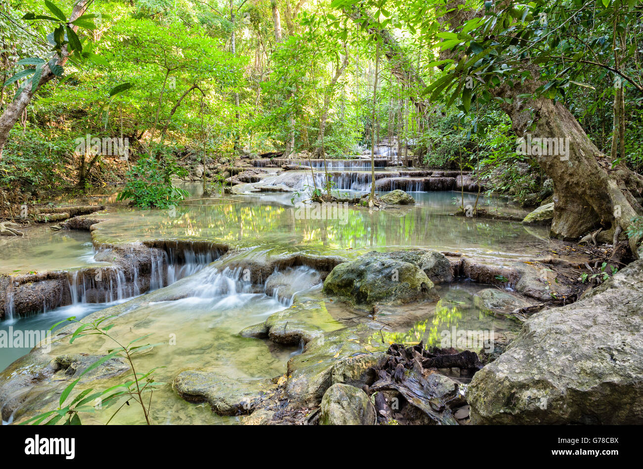 Beautiful waterfall and tropical forests at Erawan National Park is a famous tourist attraction in Kanchanaburi - Stock Image