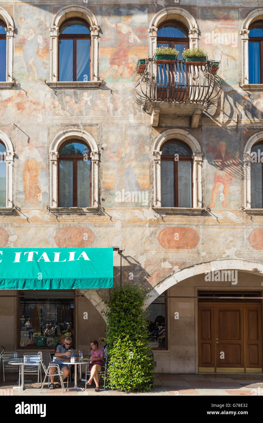 A cafe at the base of a lavishly painted Renaissance building in the main Piazza of the town of Trento in northern - Stock Image