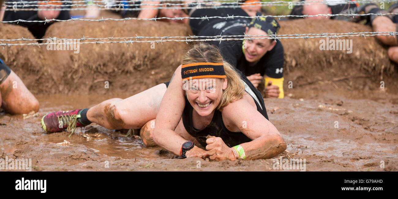 Tough Mudder, a muddy wet girl takes on the Kiss of Mud obstacle at Drumlanrig Castle, Dumfries and Galloway, Scotland, Stock Photo
