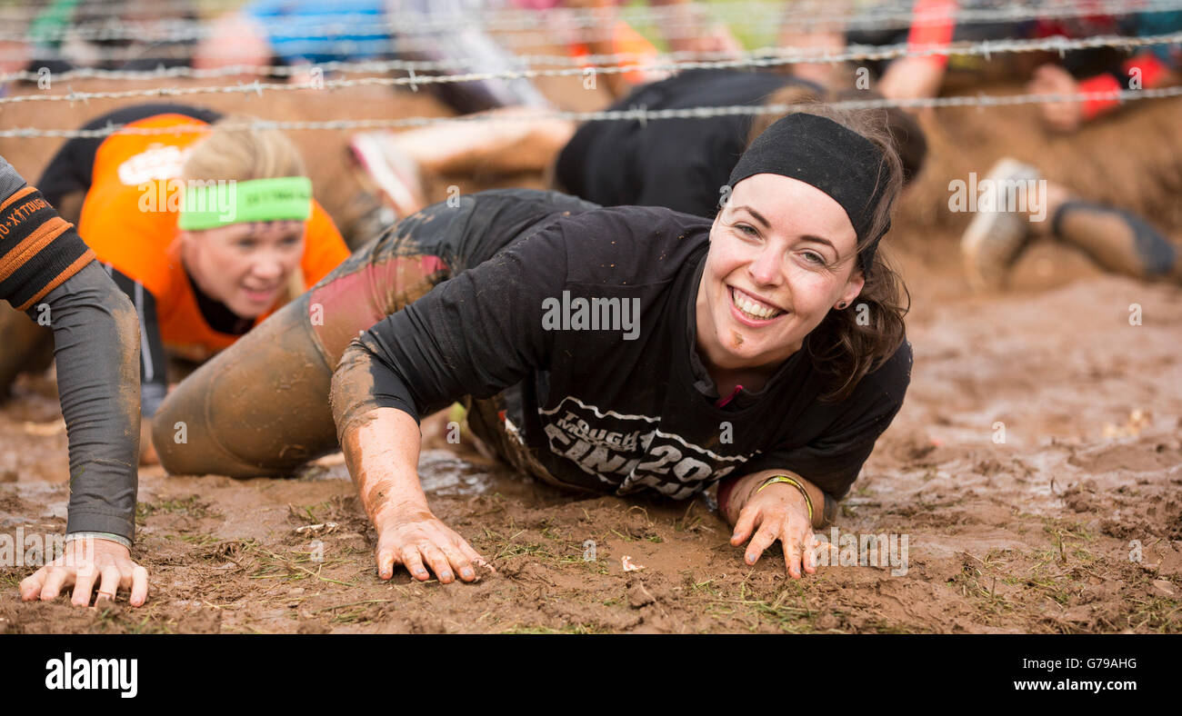 Tough Mudder obstacle course, girl smiling in mud on the Kiss of Mud obstacle Drumlanrig Castle, Dumfries and Galloway, Stock Photo