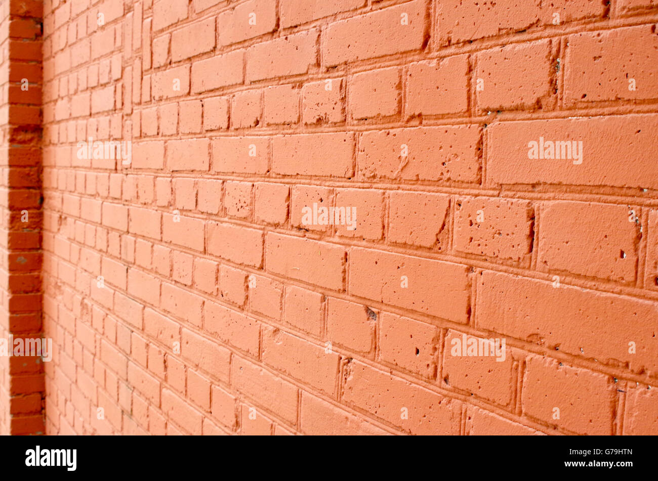 Angle view of a brick wall with a layer of red paint with blurred long-range plan to use as a background. - Stock Image