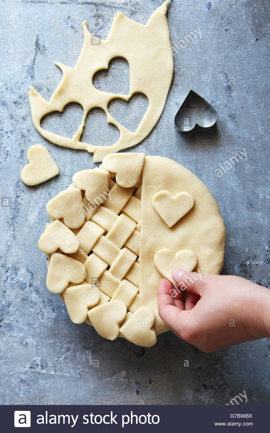Making pastry crust pie with lattice and heart shape dough.Top view. - Stock Image