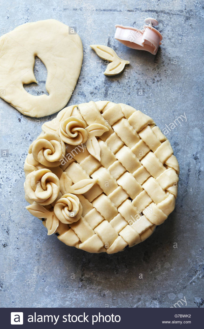 Making short crust pastry pie with lattice and leaves and roses.Top view. - Stock Image