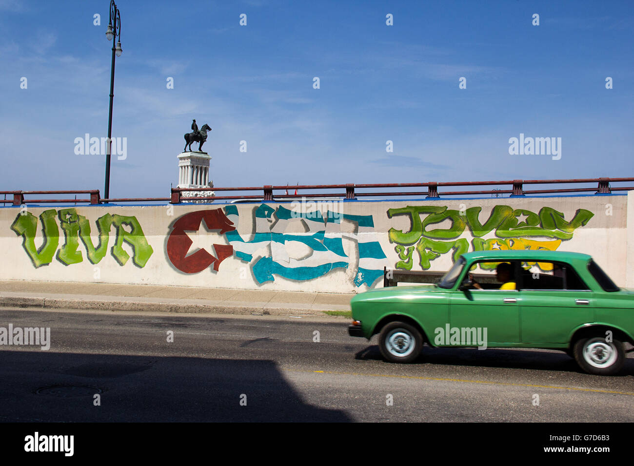 An old car passes in front of a graffiti in a street of Havanas downtown on October 7, 2014 in Havana Stock Photo