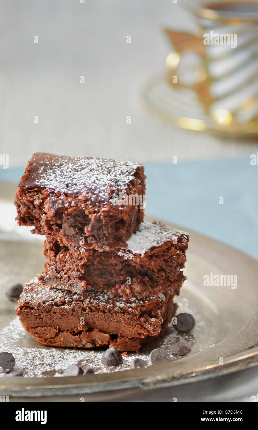 Three chocolate brownies on a fancy setup - Stock Image