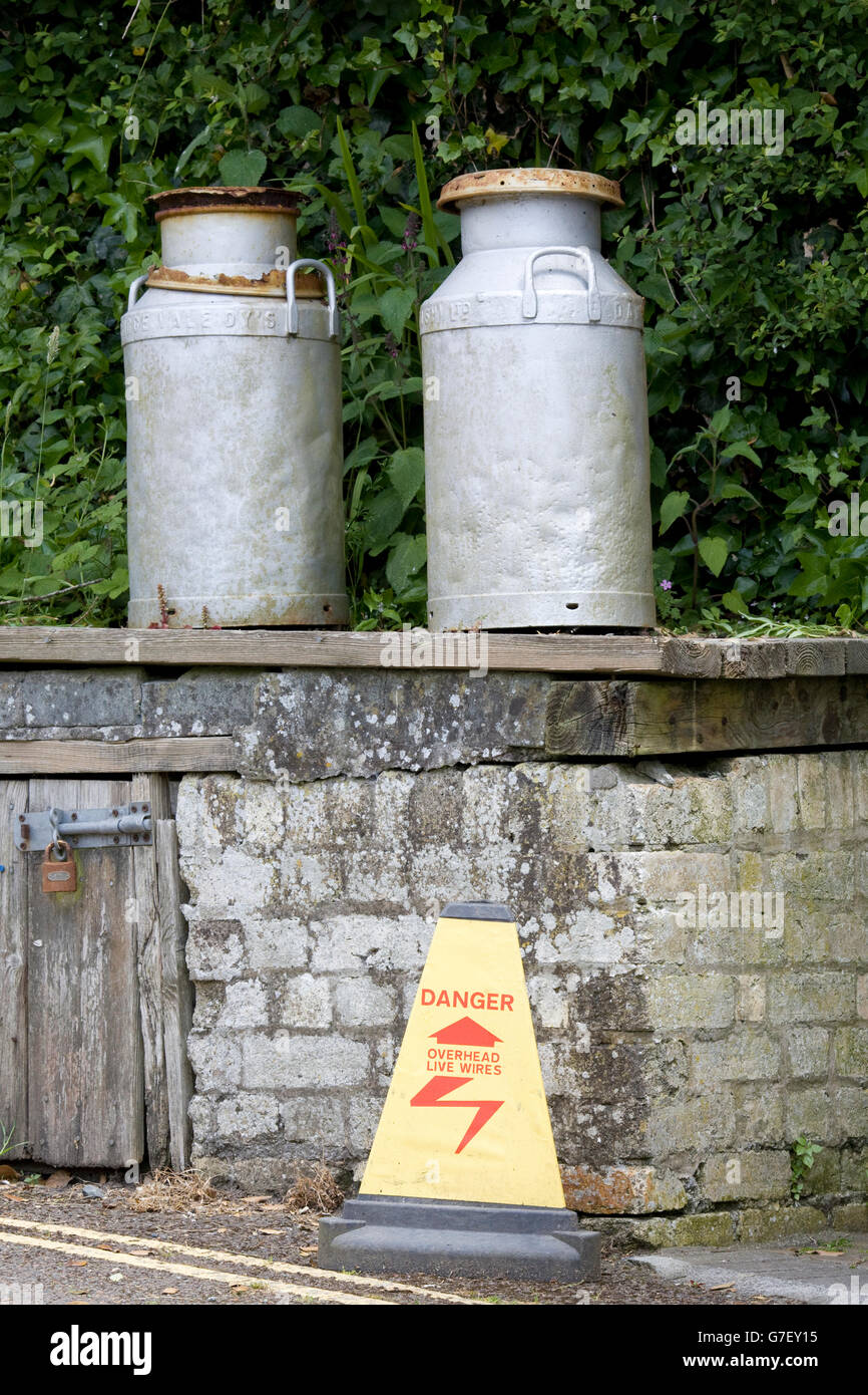 old milk churns on a brick wall with a warning sign 'Danger overhead cables' - Stock Image