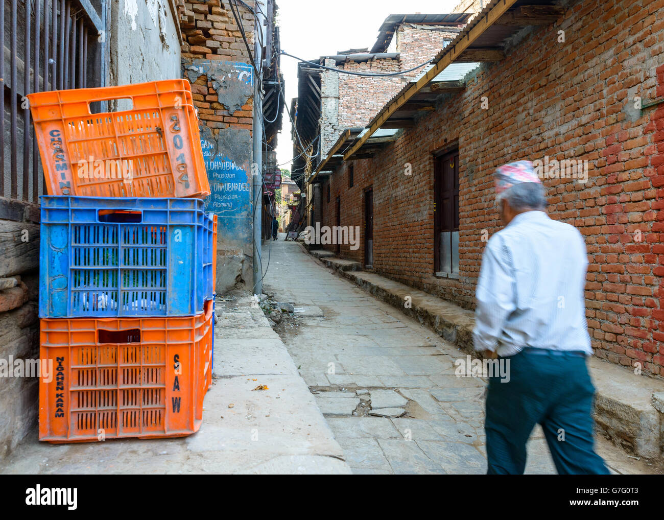 Nepalese man wearing a topi walks down a small alley in Bhaktapur, Nepal. - Stock Image