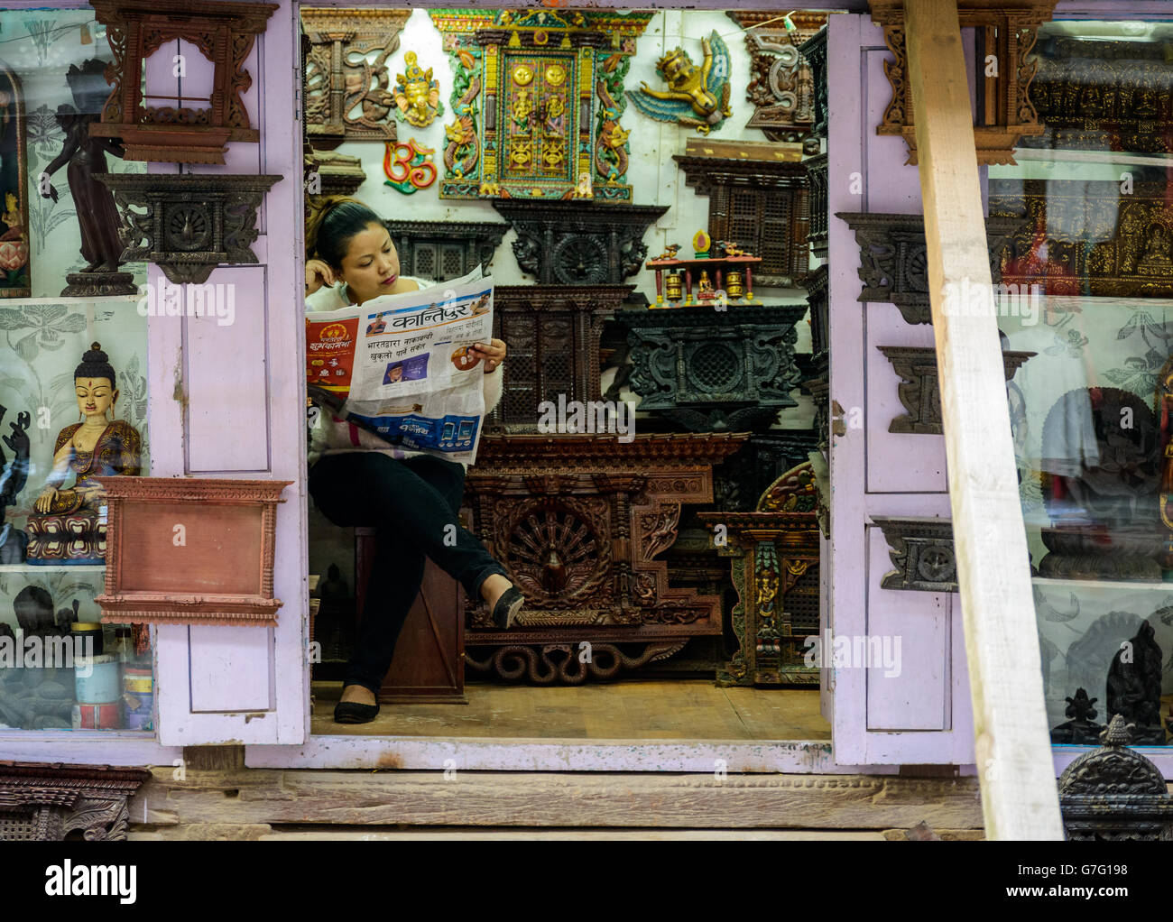 Shopkeeper reading a newspaper in Patan, Nepal - Stock Image