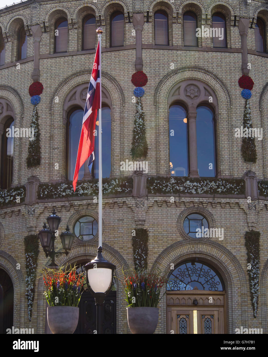 The Norwegian flag on a sunny flagpole in front of the parliament, Stortinget, in Oslo Norway - Stock Image