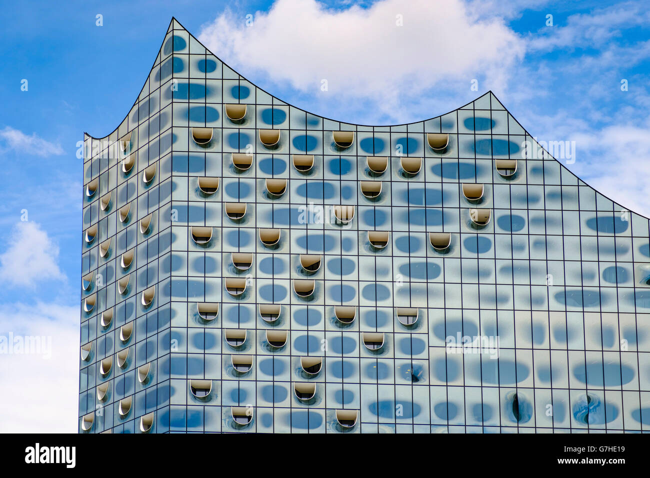 View of abstract glass facade new Elbphilharmonie concert hall nearing completion on River Elbe in Hamburg Germany - Stock Image