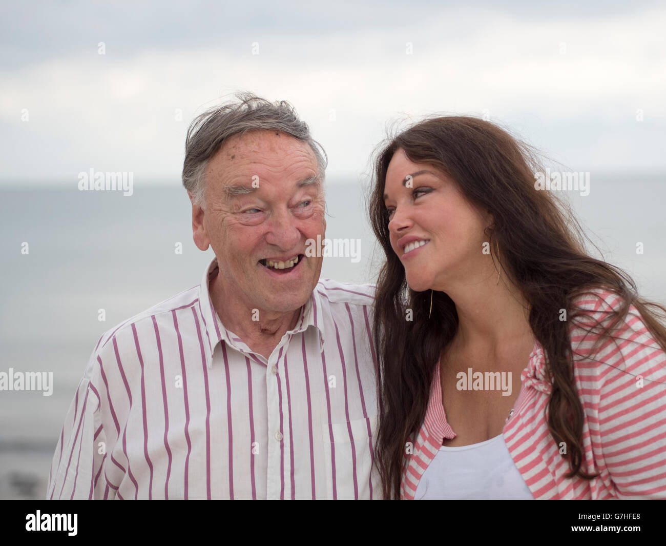 An old man and his niece enjoying a joke at the seaside. - Stock Image