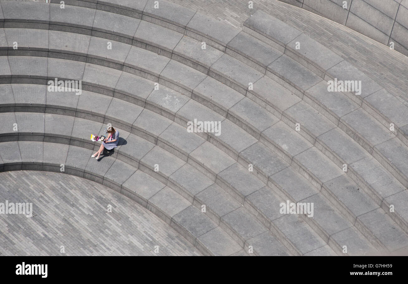 2016 London Mayoral Elections, member of staff has lunch break in The Scoop amphitheatre below City Hall in London. - Stock Image
