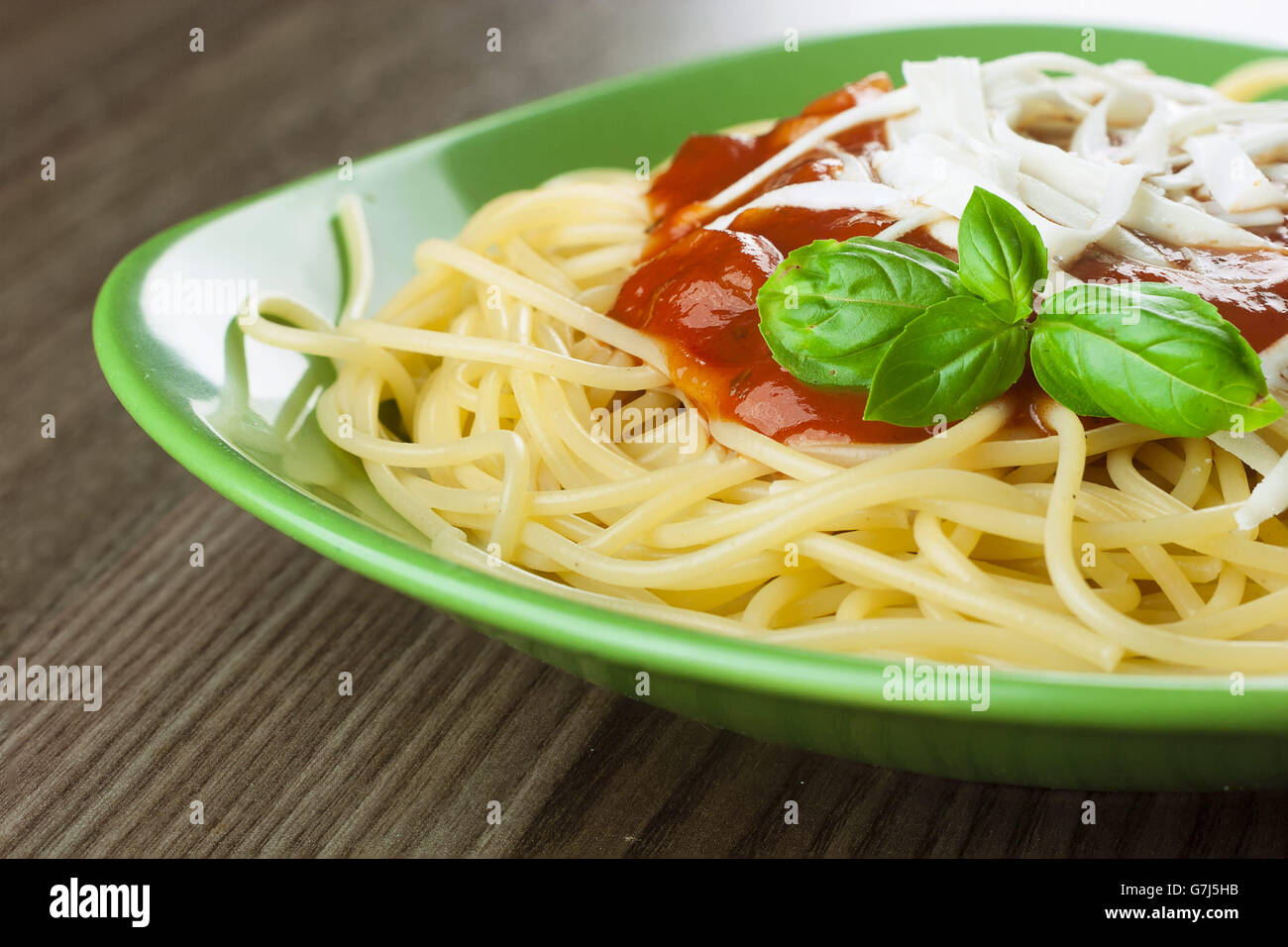 Cooked spaghetti with traditional Italian tomato souse served in a green plate on a wooden table - Stock Image