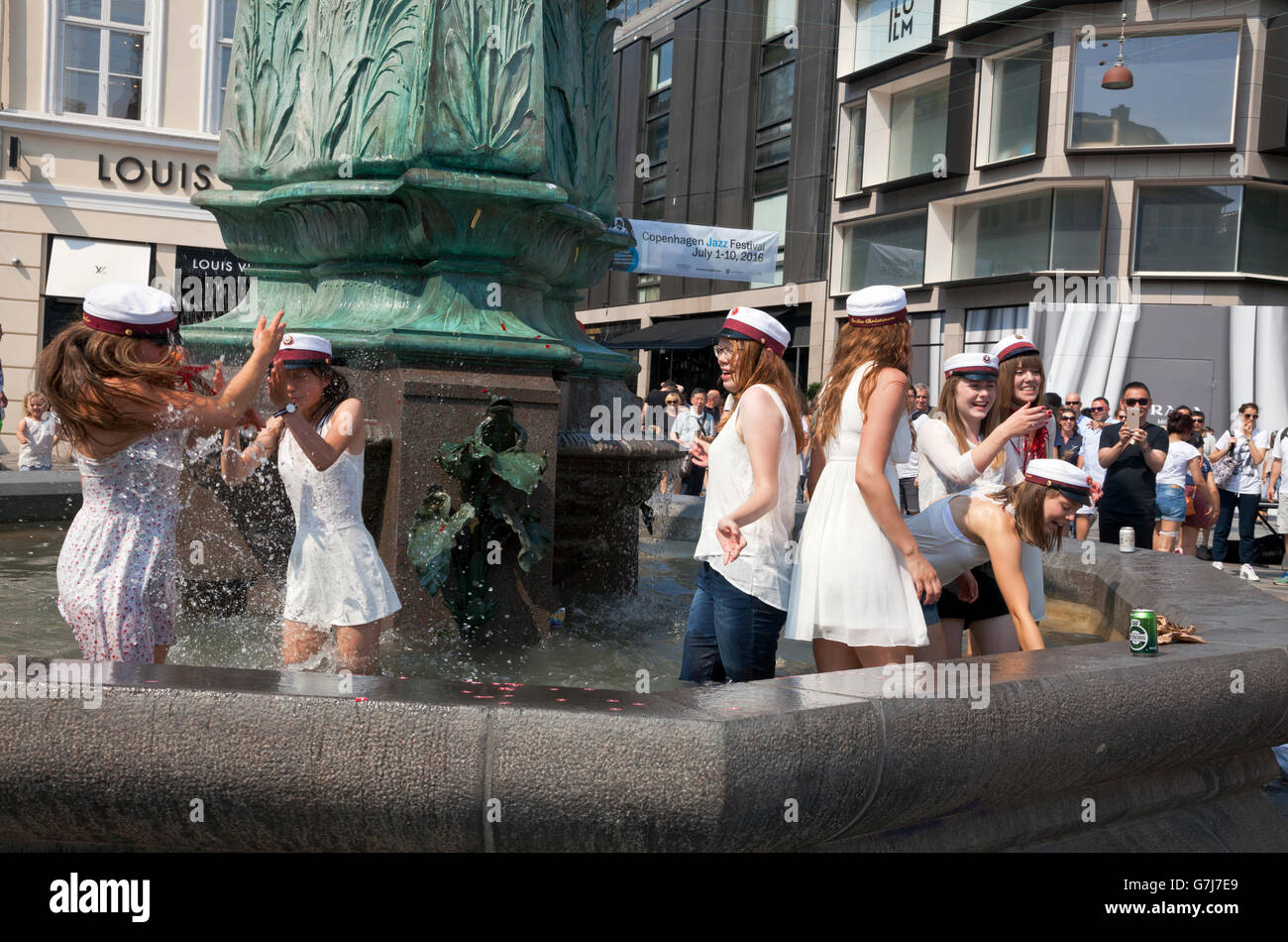 Happy Danish students celebrate their high school graduation with the traditional dip in the Stork Fountain on Stroeget - Stock Image