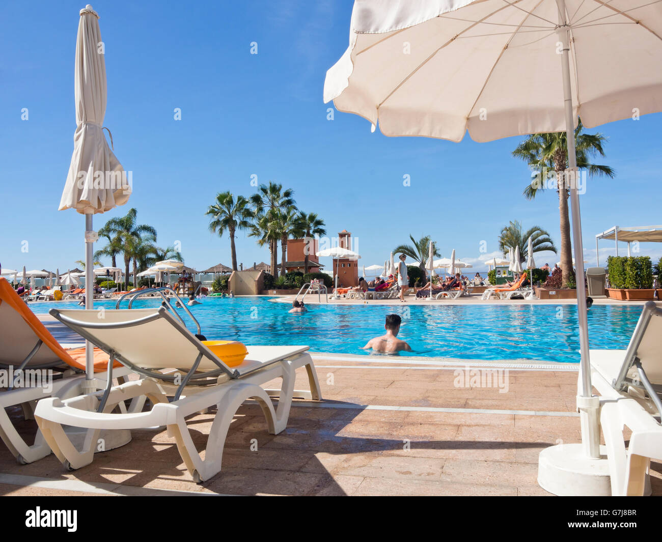 Dream holiday for many pale British holiday-makers, a poolside sunbed in Tenerife Canary islands Spain with clear - Stock Image