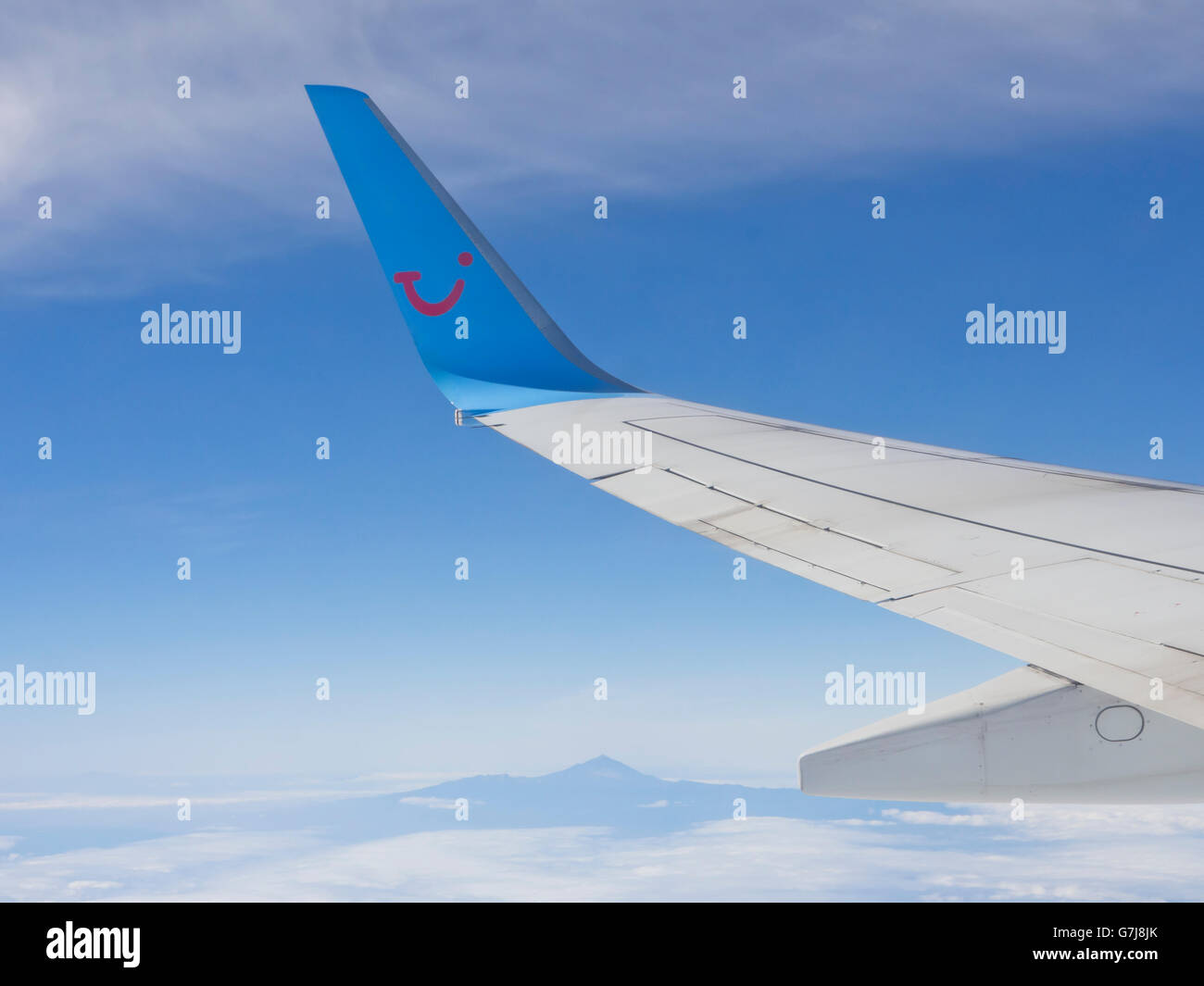 Blended winglet on a Boing airplane, smiling TUI logo in blue and red, taking passengers to or from Tenerife seen - Stock Image