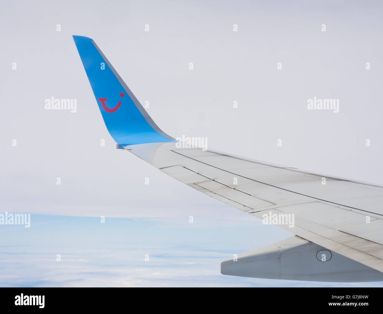 Blended winglet on a Boing airplane, smiling TUI logo in blue and red, taking passengers to or from a packaged holiday - Stock Image