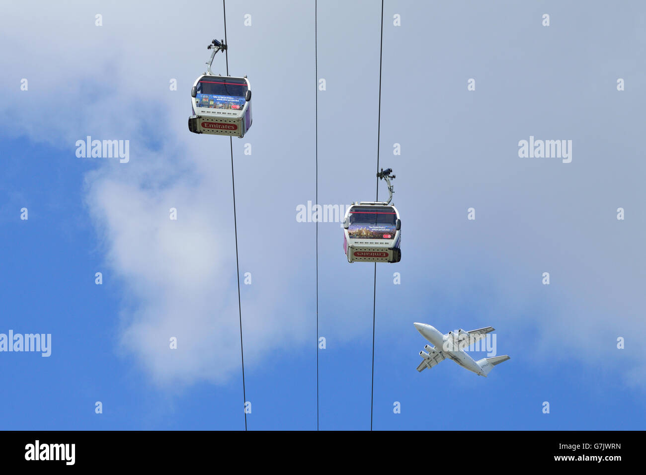 A plane takes off from London City Airport and passes over the TfL Emirates Air Line cable car at  London's - Stock Image