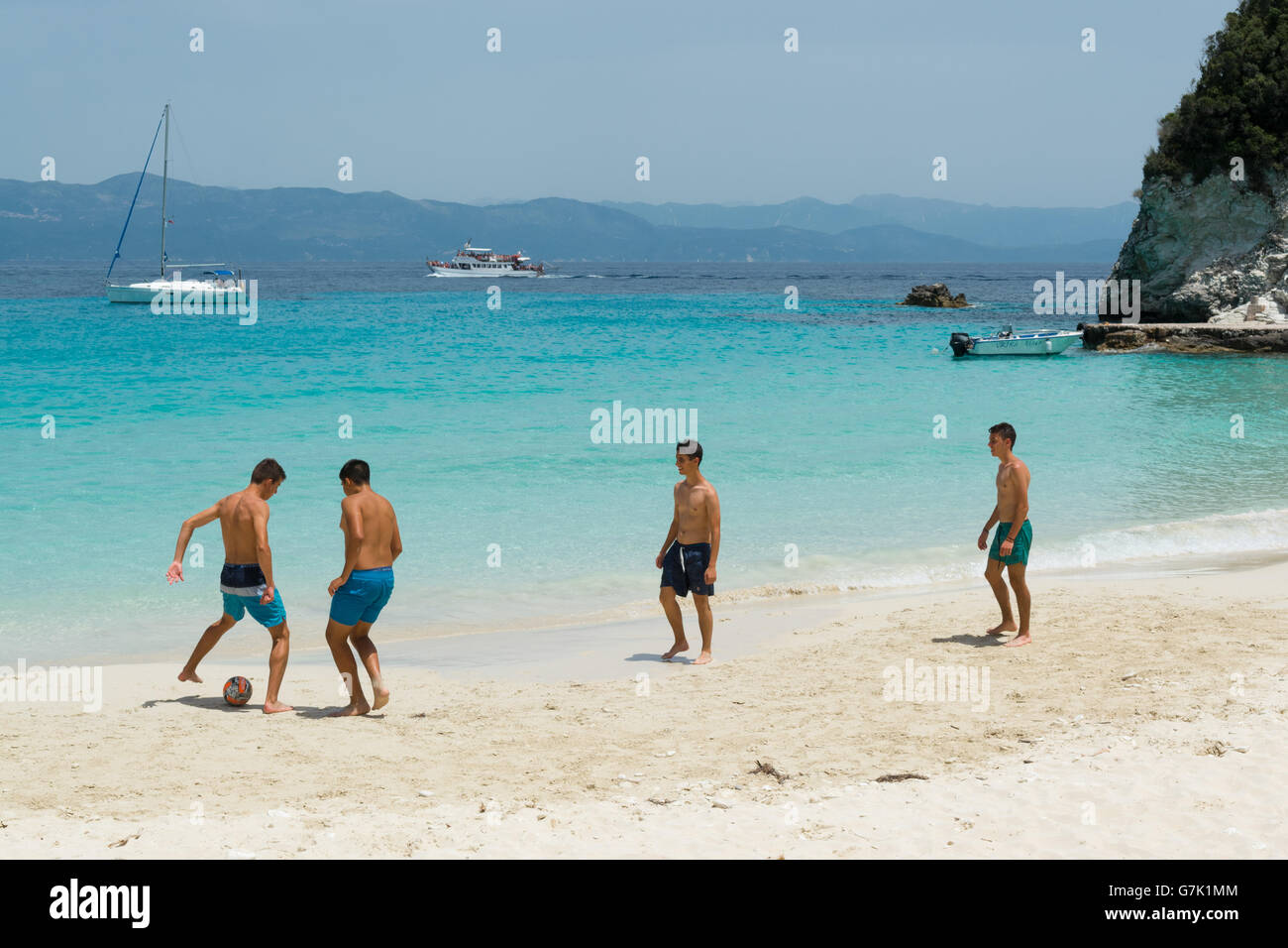 group of young men playing football on beautiful sandy Vrika beach, on the tiny island Antipaxos, Ionian Islands, - Stock Image