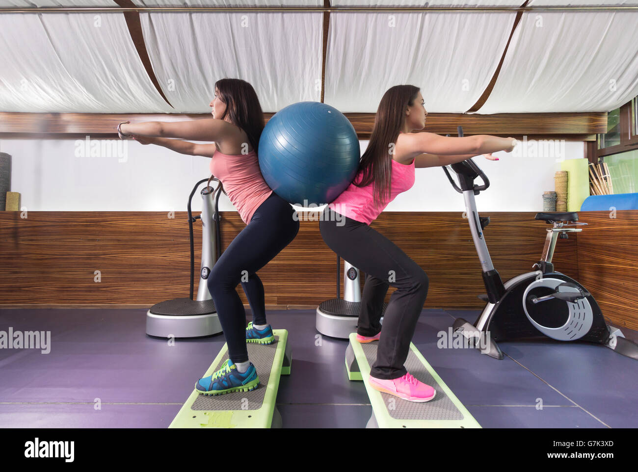 Two women gym exercise ball backs. side view. - Stock Image
