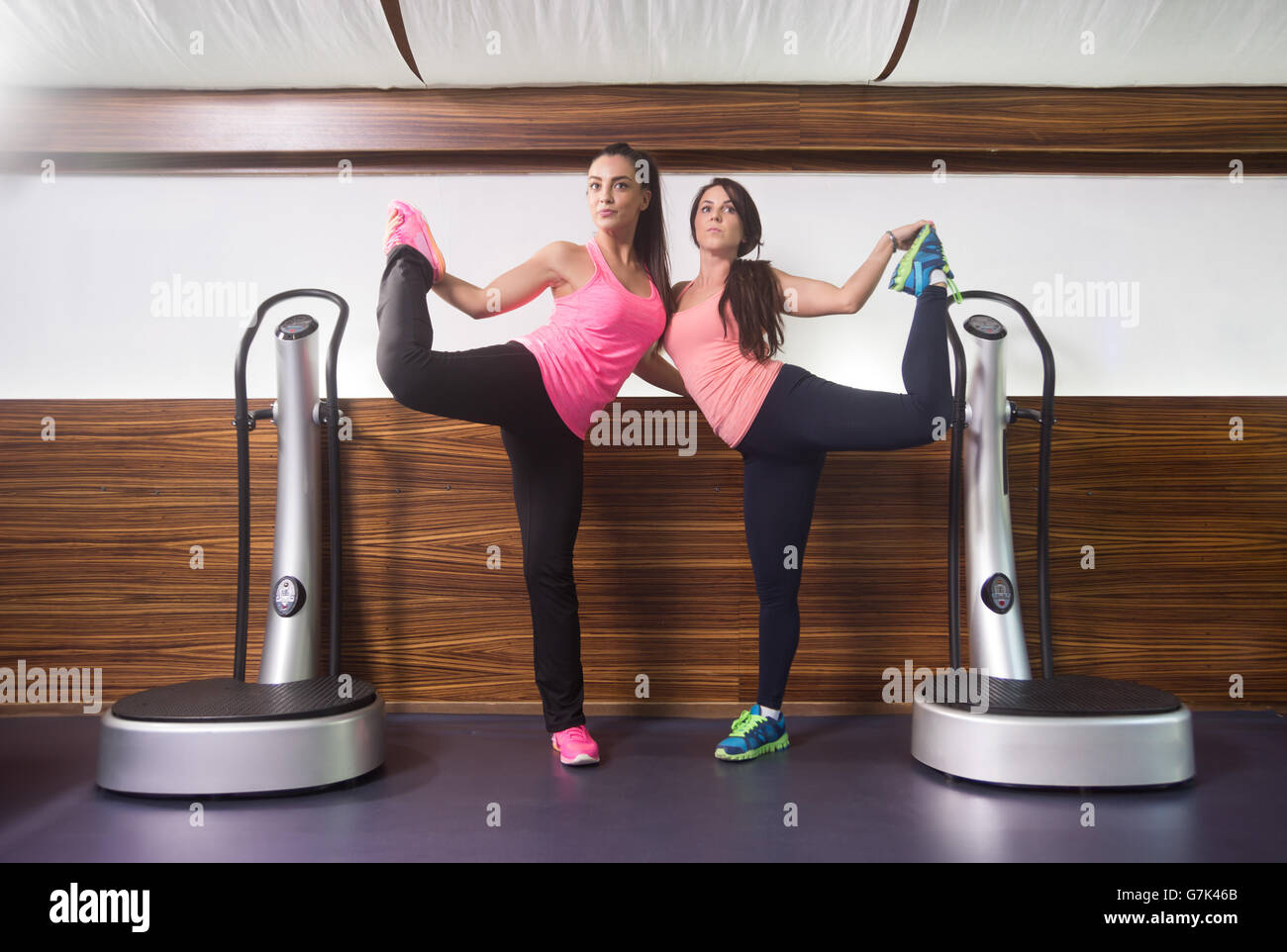 Two women standing on one leg holding feet stretching. Similar identical pose, mirroring each other. - Stock Image