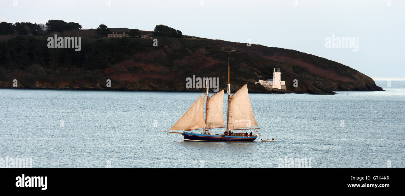 A 2-masted yacht sailing into Carrick Roads past St. Anthony's Head, Cornwall, England, UK. Stock Photo
