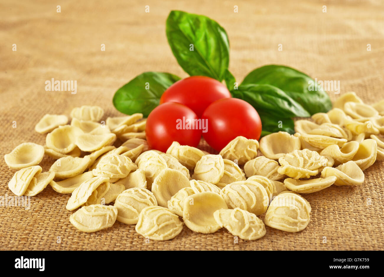 Orecchiette tomatoes and basil on jute Stock Photo