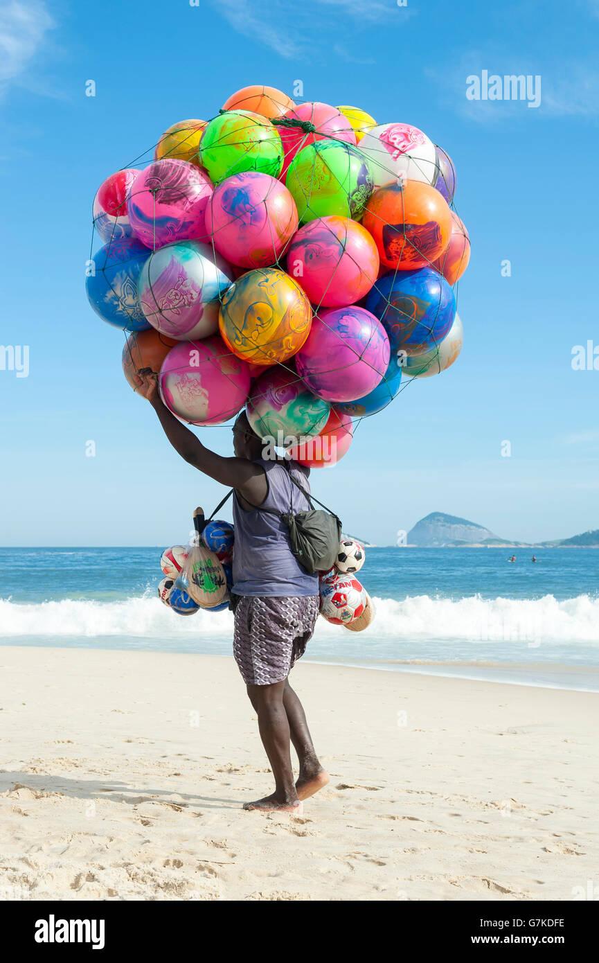 RIO DE JANEIRO, BRAZIL - JANUARY 20, 2013: Beach vendor selling colorful beach balls carries his merchandise along - Stock Image