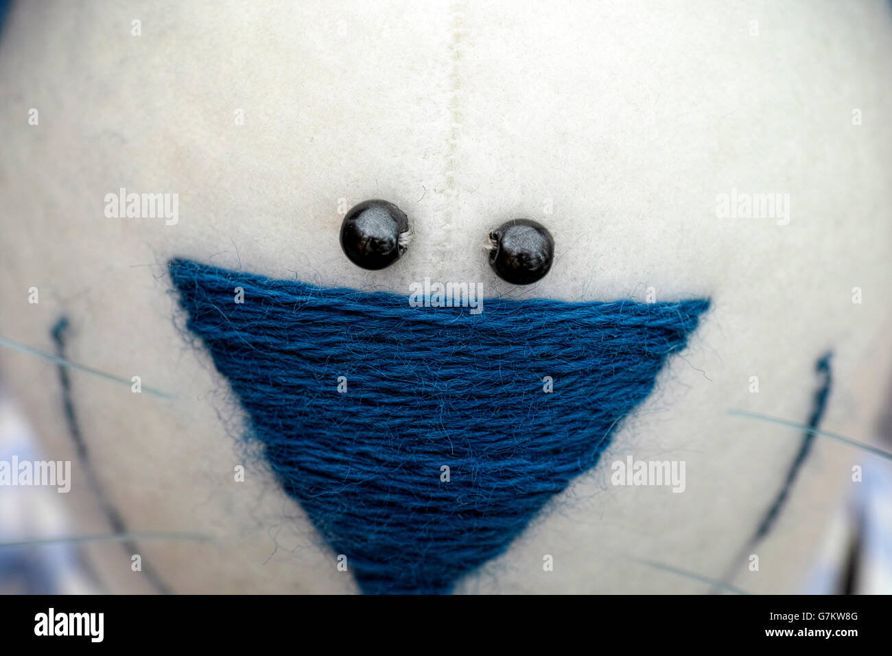Closeup of toy face with blue embroidered nose and black bead eyes - Stock Image