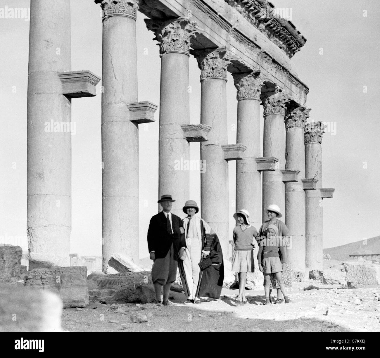 Palmyra, Syria. Visitors standing in front of part of The Great Colonnade c.1920-1933. - Stock Image