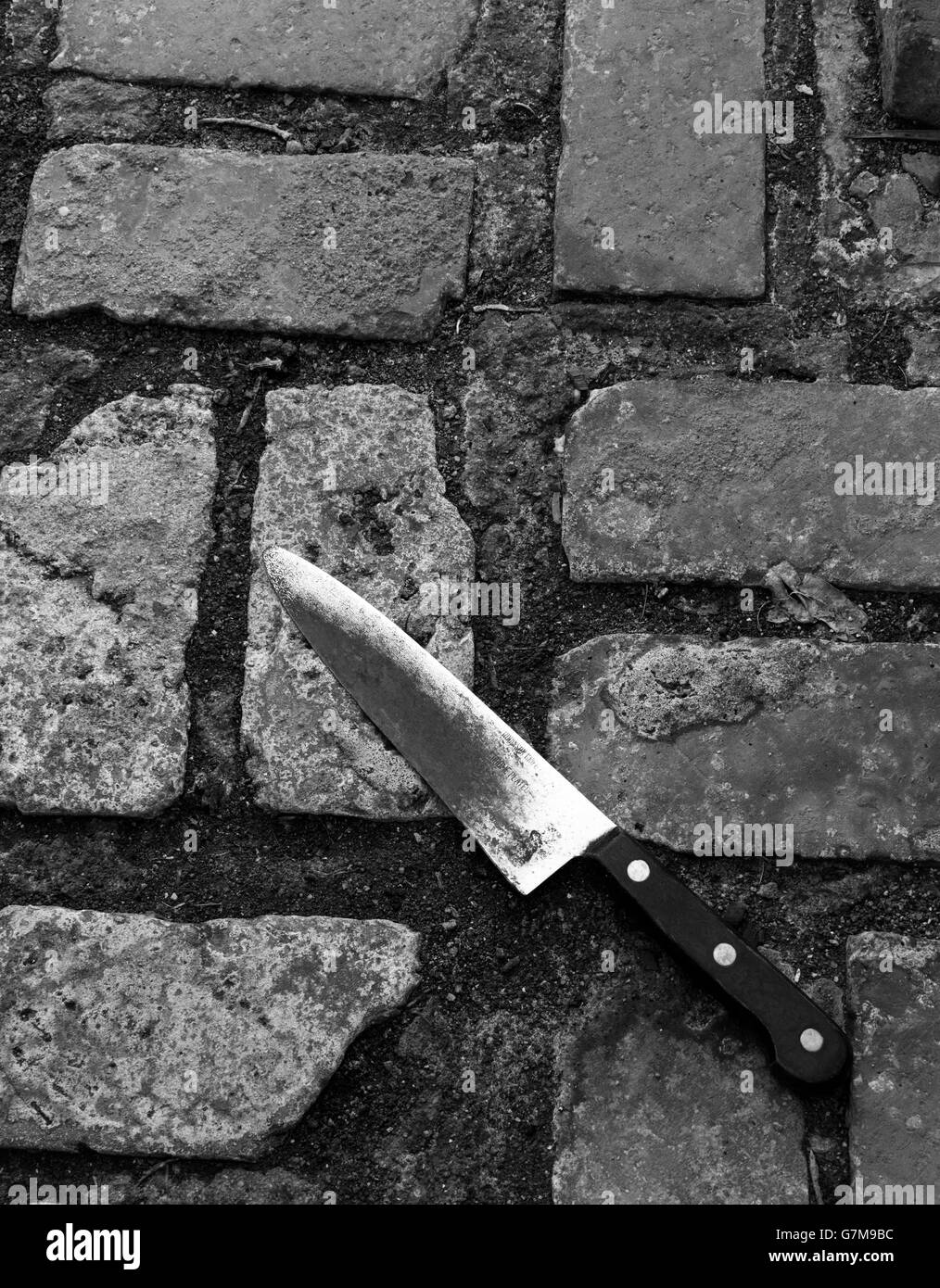 Knife laying on brick paving - Stock Image