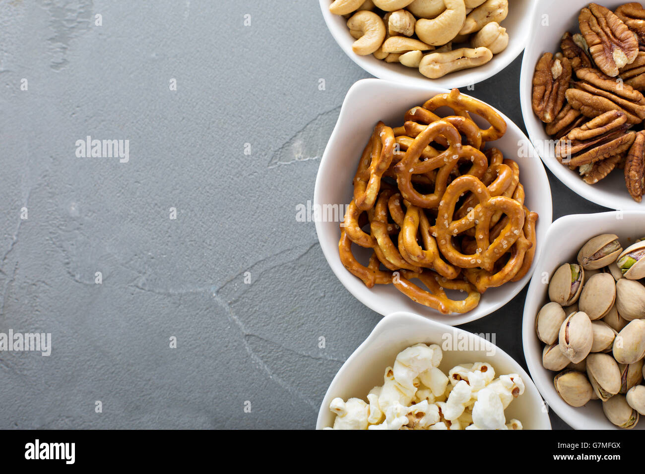 Variety of healthy snacks in white bowls - Stock Image