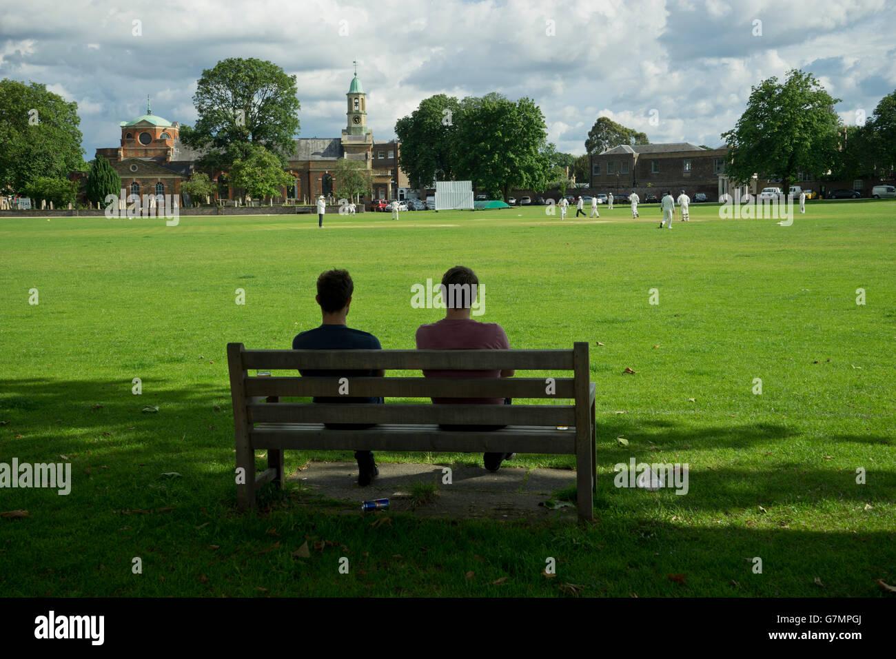 People watch cricket game in Kew Green, London, UK - Stock Image