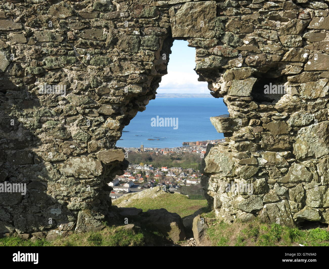 a gap in an old abandoned house looking out onto the sea in Edinburgh - Stock Image