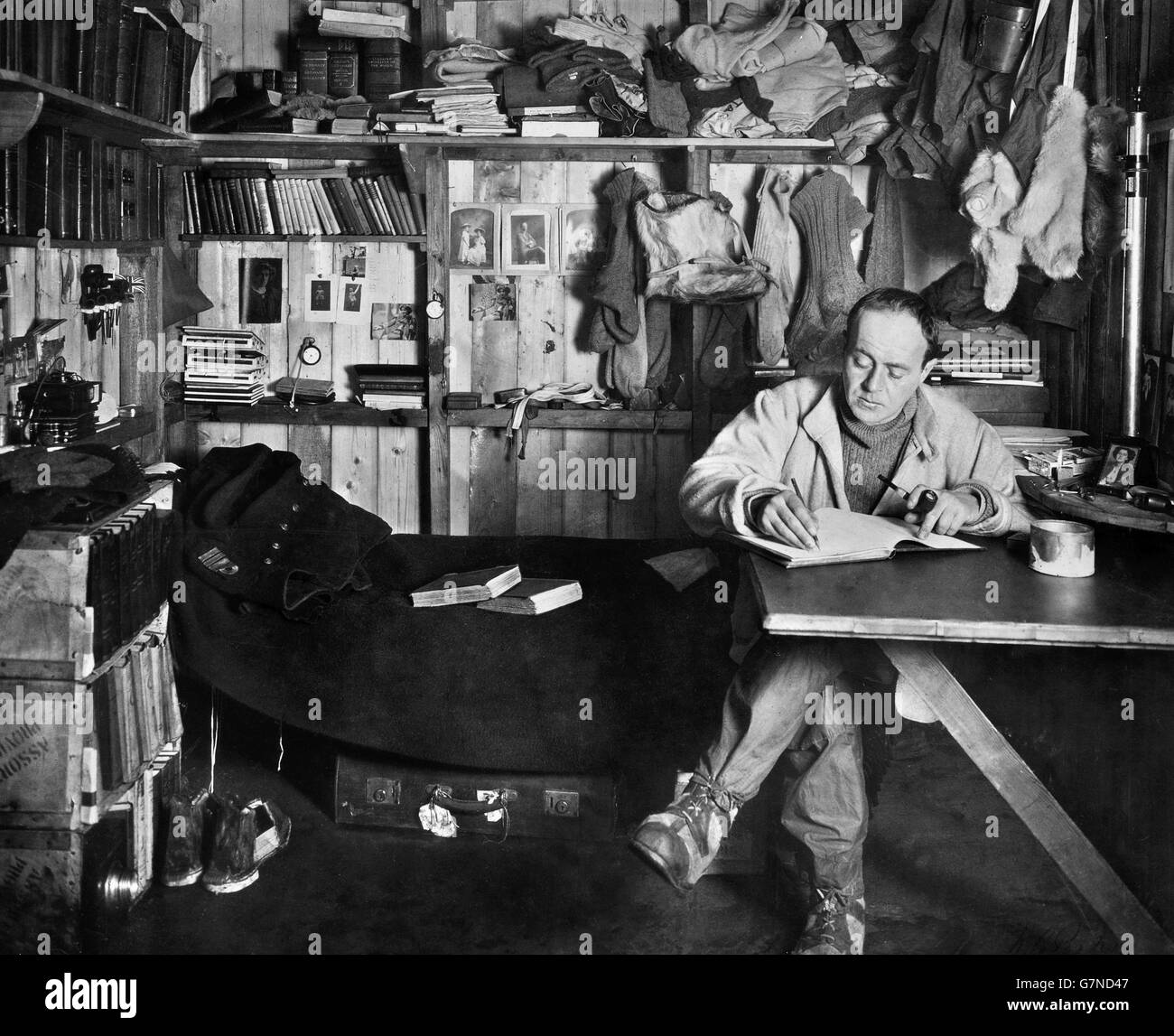 Captain Robert Falcon Scott writing in his diary in his hut at Cape Evans, Ross Island during the Terra Nova Expedition - Stock Image