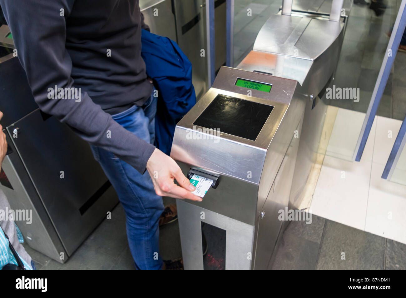 Man inserting a ticket into a ticket checking machine to get access to the Barcelona metro system. - Stock Image