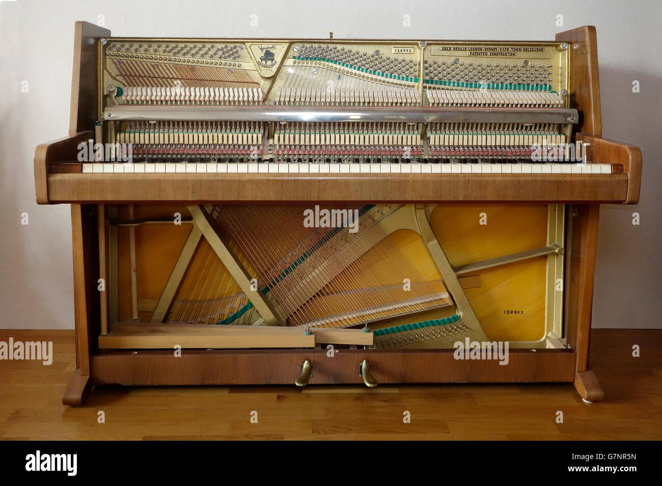 Dismantled upright piano stripped from front doors and fall showing inner mechanisms and strings. & Dismantled upright piano stripped from front doors and fall showing ...