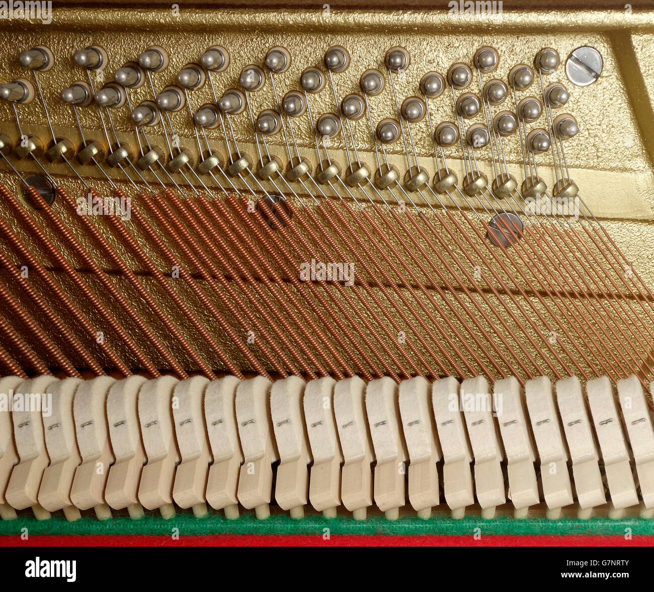 Close up of action mechanism  on an upright piano with hammers, bass strings, pressure bar and tuning pins Stock Photo