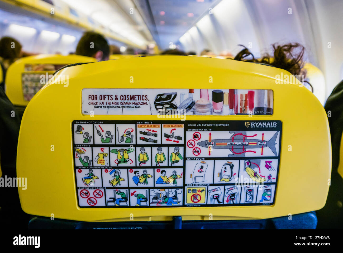 Emergency evacuation information on the back of a yellow headrest on a Ryanair airplane.  Ryanair have no safety - Stock Image