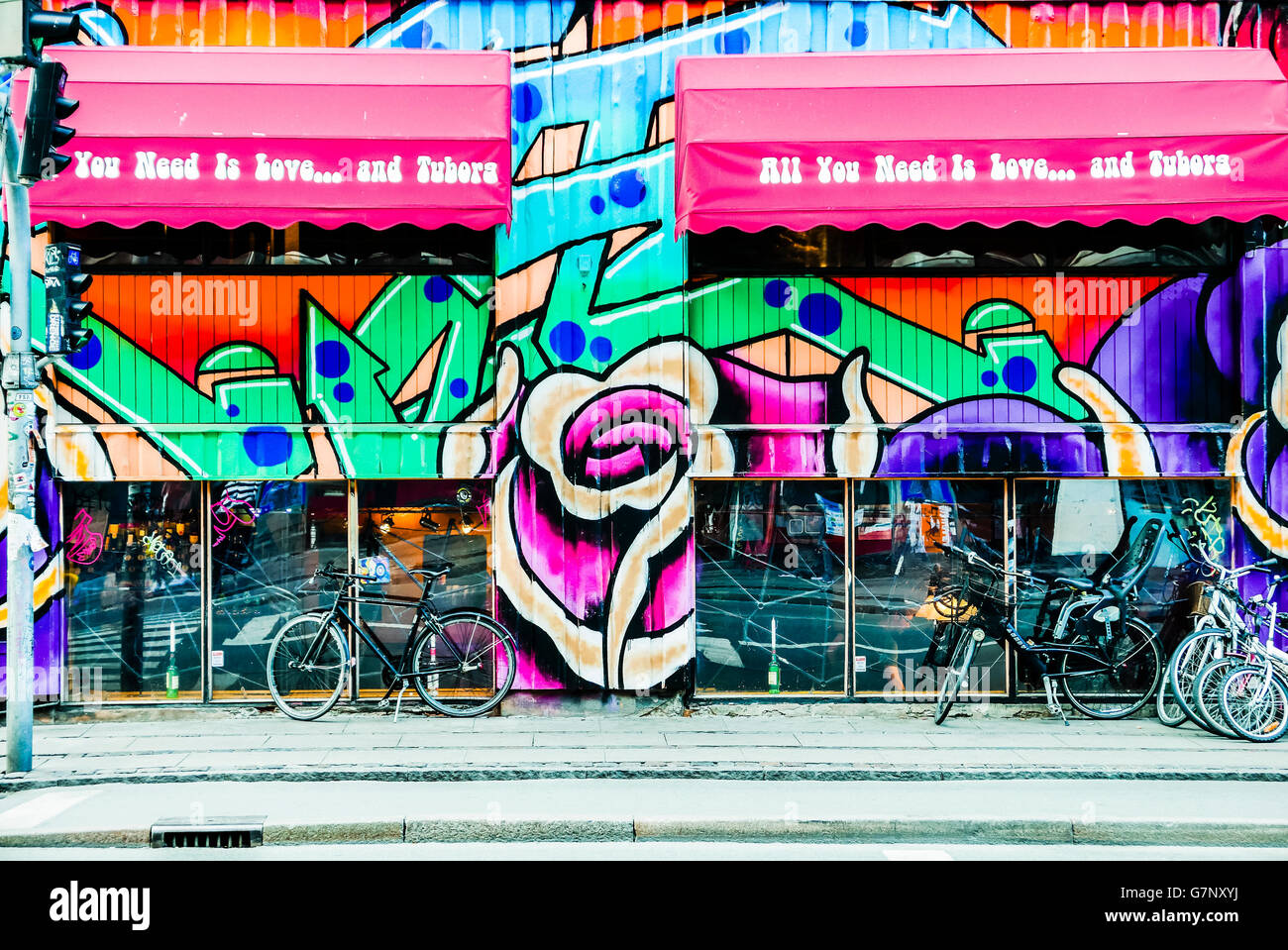 Graffiti and bicycles outside a bar in Copenhagen, Denmark with the motto 'All you need is love... and Tuborg'. - Stock Image