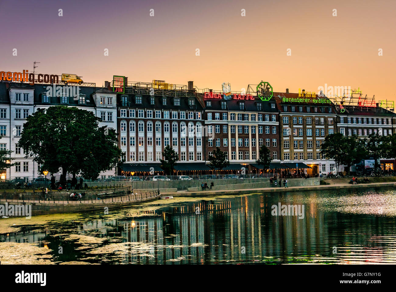 Buildings with neon advertising signs on the roofs beside the Sortedams Sø, Copenhagen, during sunset. - Stock Image