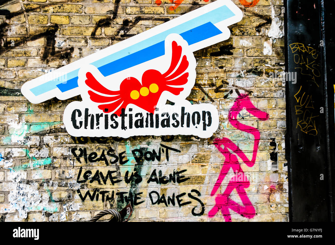 Sign outside a shop in Freetown Christiania, Copenhagen, with the message 'Please don't leave us alone with - Stock Image